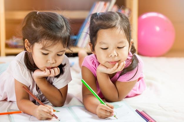 Mignonnes Petites Filles Asiatiques Dessinent Avec Leurs Crayons. Tonalité De Couleur Vintage Photo Premium