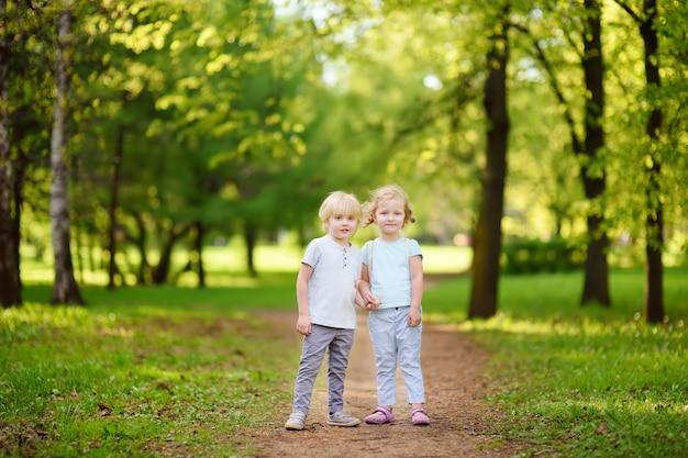 Mignons Petits Enfants Jouant Ensemble Et Se Tenant La Main Dans Le Parc De L'été Ensoleillé Photo Premium