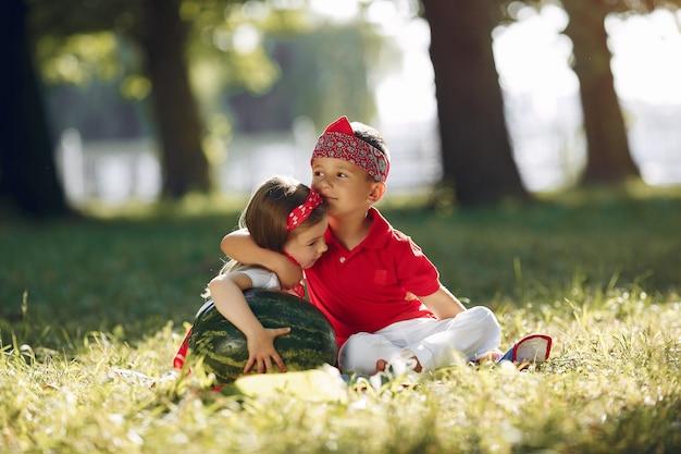 Mignons petits enfants avec des pastèques dans un parc Photo gratuit