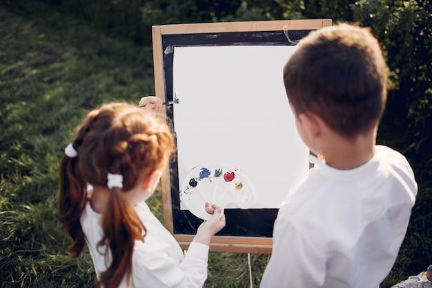 Mignons petits enfants peignant dans un parc Photo gratuit