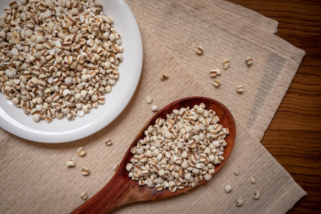 Mil dans une cuillère en bois qui est des céréales et de la nourriture sur une nappe brune Photo Premium