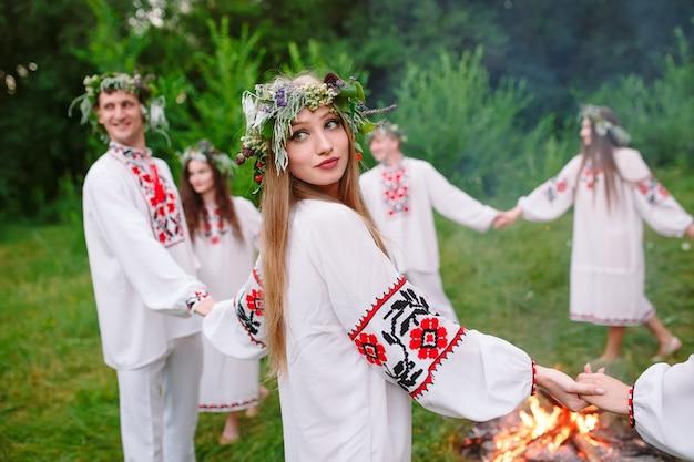 Milieu de l'été. les jeunes en vêtements slaves tournent autour d'un feu en plein été. . Photo Premium