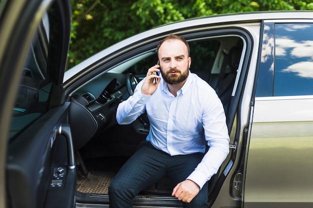 Milieu homme adulte assis dans une voiture avec la porte ouverte, parler sur smartphone Photo gratuit