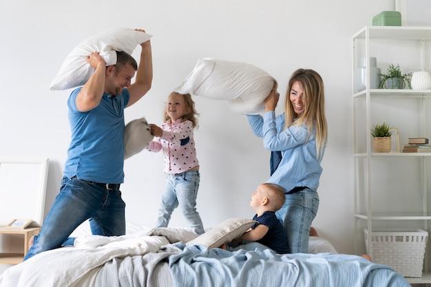 Milieu des membres de la famille se battre avec des oreillers Photo gratuit