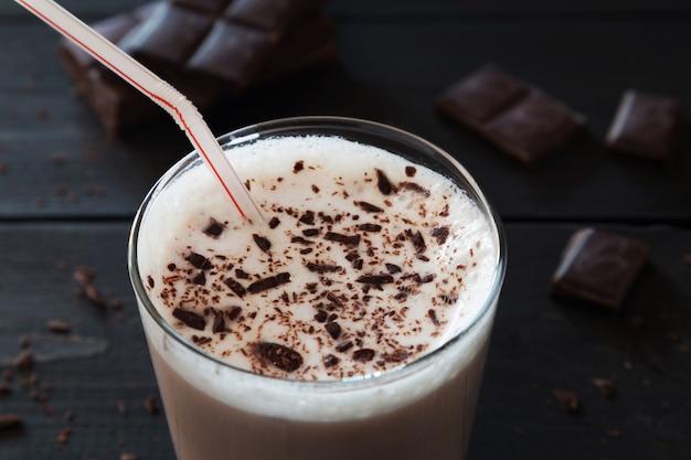 Milk-shake au chocolat et miettes de chocolat sur un arr.plans en bois Photo Premium