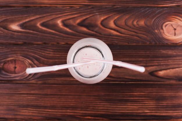 Milkshake en bouteille sur une surface en bois Photo gratuit