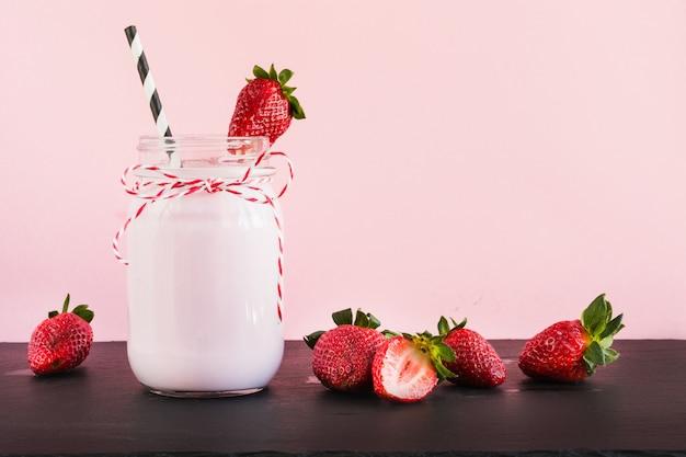 Milkshake à la fraise avec des baies dans un bocal en rose. fermer. boisson d'été. Photo Premium