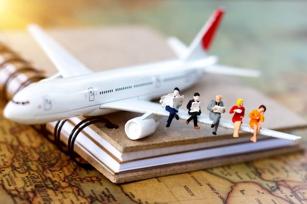 Minature people: voyager avec un livre de lecture dans l'avion. Photo Premium