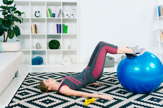 Mince jeune femme faisant de l'exercice avec ballon bleu de pilates sur tapis à la maison Photo gratuit