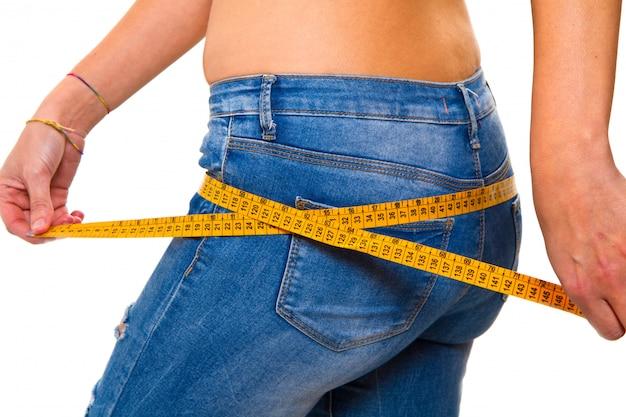 Une mince jeune femme en jeans avec un ruban à mesurer après une réussite Photo Premium