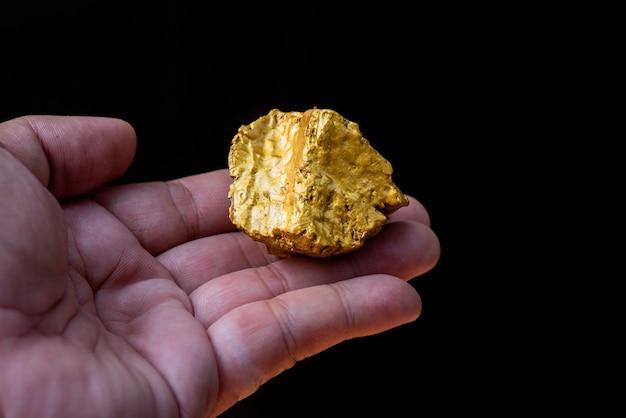Le minerai d'or trouvé dans la mine est dans la main Photo Premium