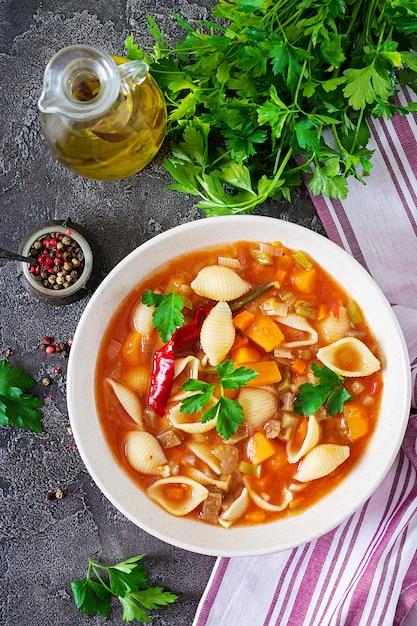 Minestrone, Soupe Aux Légumes Italienne Avec Des Pâtes Sur La Table. Nourriture Végétalienne. Vue De Dessus Photo Premium