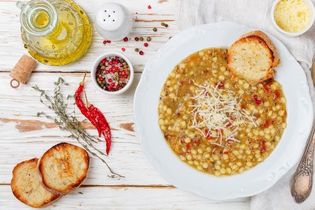 Minestrone soupe épaisse avec des légumes, des pâtes, des lentilles, du fromage et des épices, Photo Premium