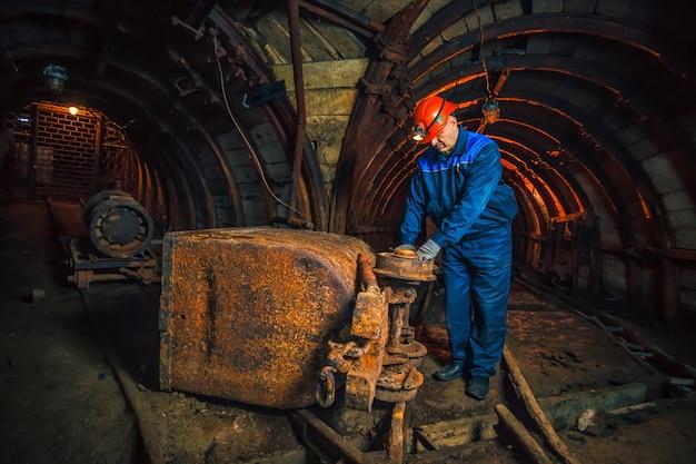 Un mineur dans une mine de charbon se trouve près d'un chariot. espace de copie. mineur en train de réparer un chariot Photo Premium