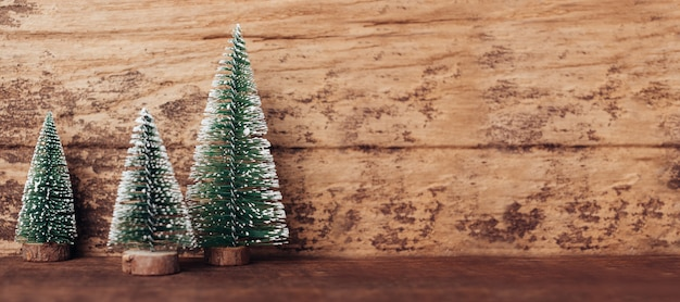 Mini arbre de noël en bois sur une table en bois rustique et mur en bois dur Photo Premium