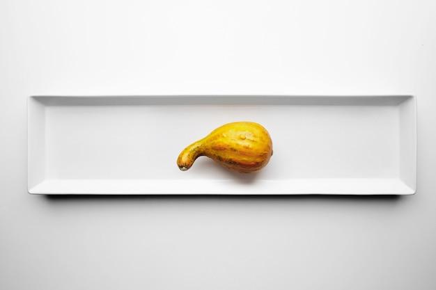 Une Mini Bouteille De Courge Isolée Sur Une Plaque En Céramique Rectangulaire Blanche Photo gratuit
