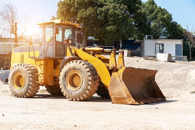 Mini bulldozer de chantier de construction de bâtiment industriel nivelant et remuant le sol pendant la construction d'une autoroute Photo Premium