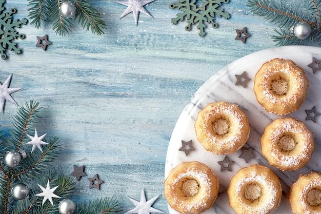 Mini bundt ring gâteaux avec du sucre glace sur fond clair avec des brindilles de sapin, des baies et des cannes de bonbon Photo Premium