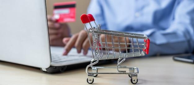 Mini chariot, homme d'affaires asiatique détenant la carte de crédit et à l'aide d'un ordinateur portable Photo Premium