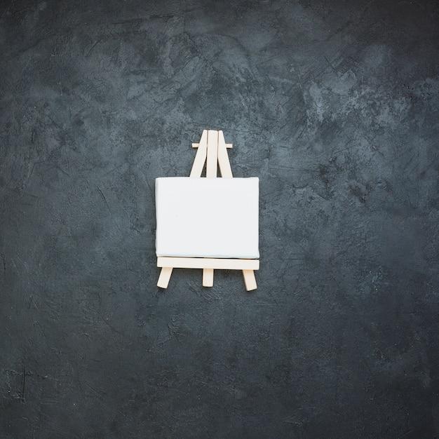 Mini chevalet vierge blanc sur une surface en ardoise noire Photo gratuit