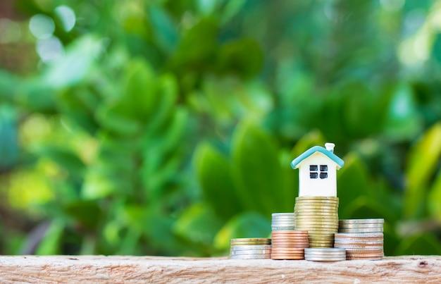 Mini maison sur pile de pièces. concept de propriété d'investissement. Photo Premium