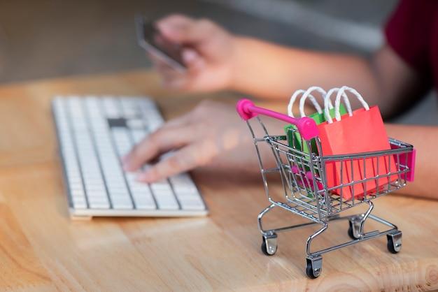 Mini panier, femme détenant une carte de crédit avec un ordinateur portable et un smartphone pour faire des achats en ligne Photo Premium
