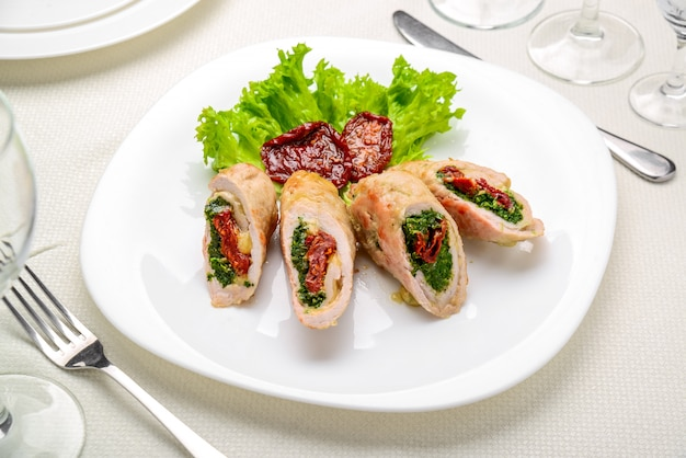 Mini roulés au poulet avec tomates séchées et épinards. plat de fête. Photo Premium