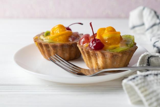 Mini tartes aux fruits avec cerise orange et kiwi sur plaque blanche. Photo Premium