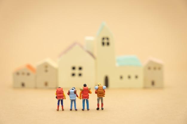 Miniature 4 personnes debout sur les modèles de maison et hôtel pour choisir un endroit pour vivre. Photo Premium