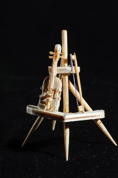 Miniature en bois de violon sur fond noir. violon debout sur un support en bois. Photo Premium