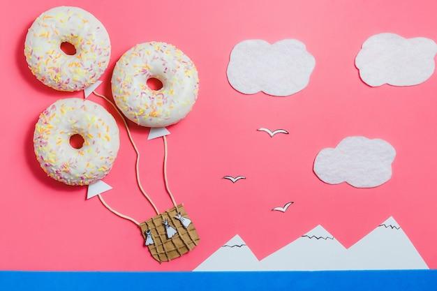 Minimalisme alimentaire créatif, beignet en forme d'aérostat dans un ciel rose avec nuages, montagnes, vue de dessus, espace de copie, voyage Photo Premium