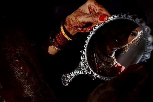 Miroir en argent dans les mains d'une mariée hindoue avec des tatouages au henné Photo gratuit