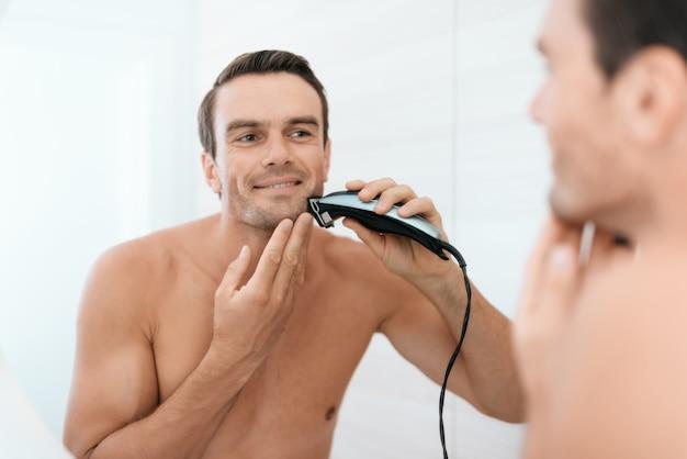 Miroir reflet de l'homme se brosser les dents dans la salle de bain Photo Premium