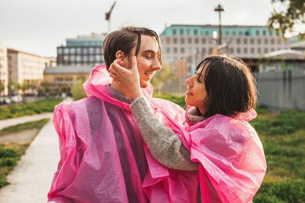 Mise Au Point Peu Profonde D'un Couple D'imperméables En Plastique Rose Se Regardant De Façon Romantique Photo gratuit