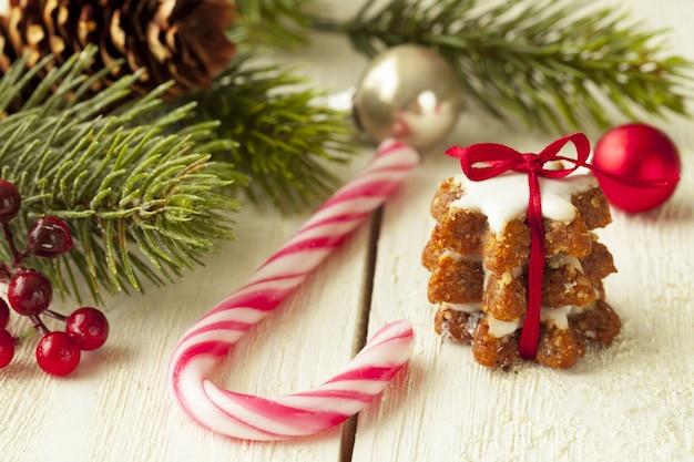 Mise Au Point Peu Profonde Gros Plan D'un Biscuit Au Gingembre à Côté D'une Canne En Bonbon Et Des Branches D'arbres De Noël Photo gratuit
