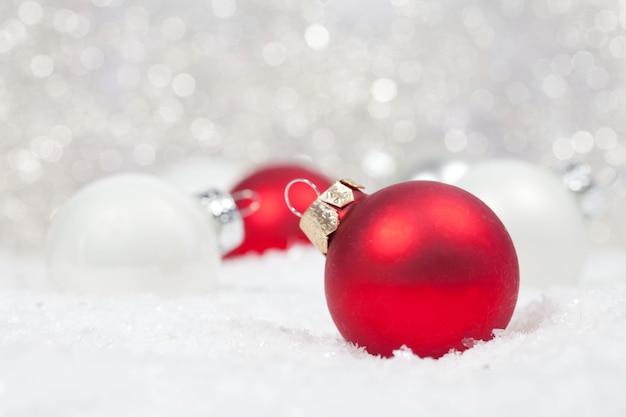 Mise Au Point Sélective Des Ampoules De Noël Rouges Et Blanches Dans La Neige Avec Des Lumières Bokeh Sur L'arrière-plan Photo gratuit