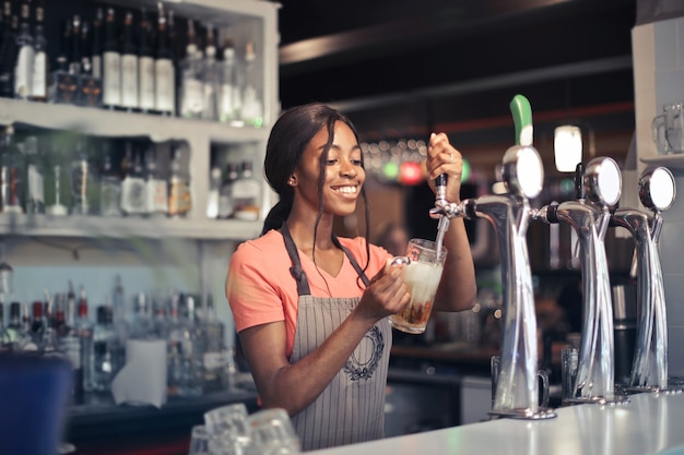 Mise Au Point Sélective D'une Femme Afro-américaine De La Bière De Remplissage De Barman à Partir D'une Pompe De Bar Photo gratuit