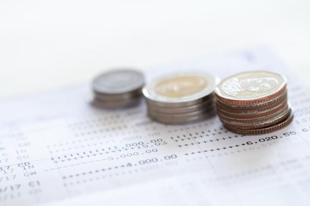 Mise au point sélective des pièces de monnaie thaïlandaises empilées sur la page du relevé de compte bancaire sur fond blanc. Photo Premium