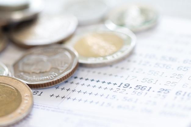 Mise Au Point Sélective Des Pièces De Monnaie Thaïlandaises Empilées Sur La Page Du Relevé De Compte Bancaire Sur Fond Blanc Photo Premium