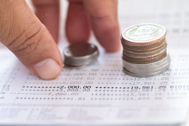 Mise au point sélective des pièces de monnaie thaïlandaises empilées sur la page du relevé de compte bancaire. Photo Premium