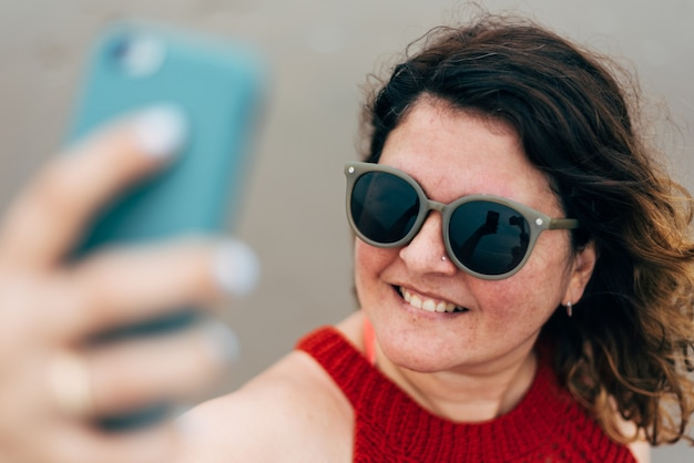 Mise Au Point Sélective D'un Portrait De Femme Souriante Portant Des Lunettes De Soleil Et Utilisant Son Téléphone Pour Parler Lors D'un Appel Vidéo. Photo Premium