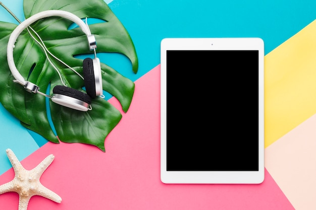 Mise en page créative de la tablette et des écouteurs Photo gratuit