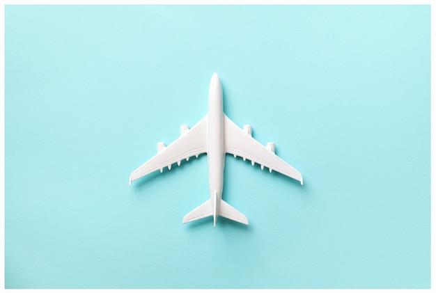 Mise en page créative. vue de dessus de l'avion modèle blanc, jouet avion sur fond pastel rose. Photo Premium