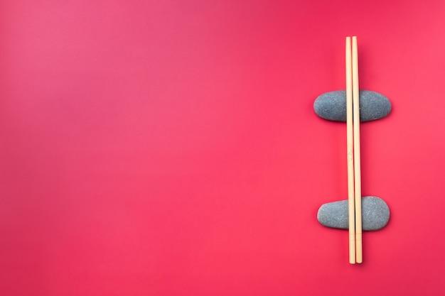 Mise à Plat. Des Baguettes En Bois Clair Reposent Sur Des Pierres Ovales Sur Fond Rose. Couverts Traditionnels Asiatiques. Copier L'espace Photo Premium