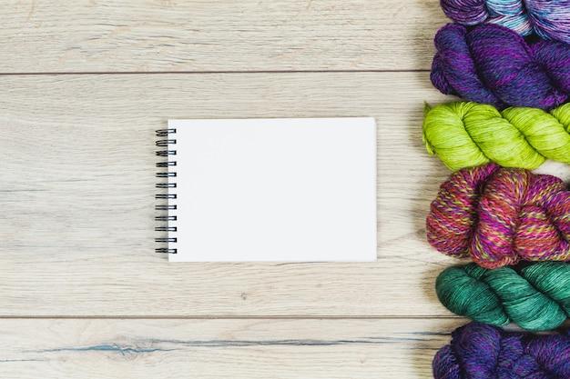 Mise à Plat De Belles échevettes Dans Des Tons Violets Et Verts Et Cahier Vierge Pour Maquette Sur Une Table En Bois Avec Espace Copie Photo Premium