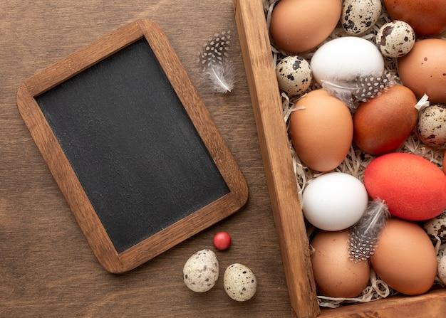 Mise à Plat De Boîte Avec Des Oeufs Pour Pâques Et Tableau Noir Photo gratuit