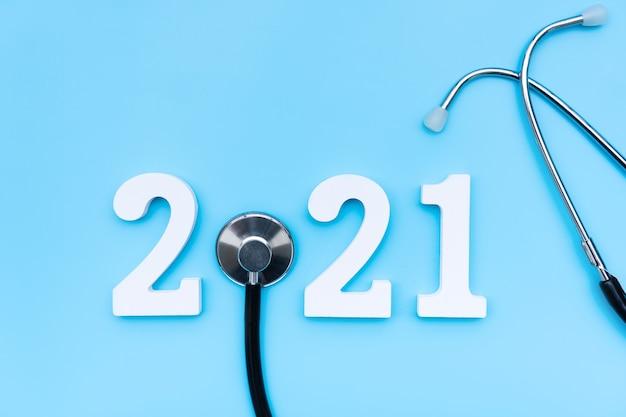 Mise à Plat De Bonne Année 2021. Numéro 2021 Avec Stéthoscope Sur Mur Bleu. Santé Médicale Et Nouveau Concept De Mode De Vie Normal. Copier L'espace, Vue De Dessus Photo Premium