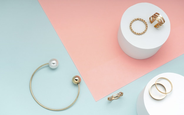 Mise à Plat De Bracelet En Or Et Perle Et Collection De Bagues En Or Sur Fond De Papier Rose Et Vert Photo Premium