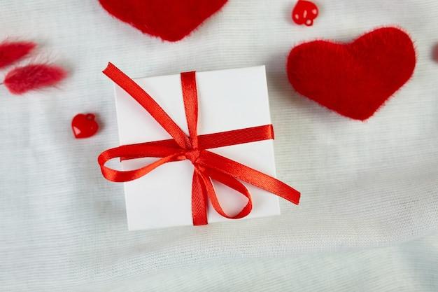 Mise à Plat De La Carte De Voeux Saint Valentin Avec Boîte-cadeau Et Coeurs Sur La Texture De Tissu Blanc Photo Premium