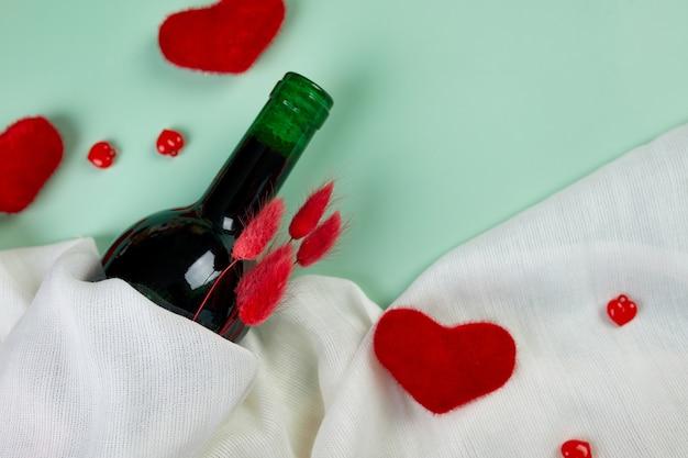 Mise à Plat De La Carte De Voeux Saint Valentin Avec Bouteille De Vin Rouge Et Coeurs Sur Bleu Photo Premium
